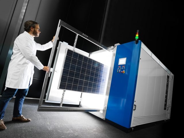 a researcher places PV module inside a temperature control solar simulator